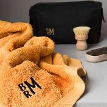 Gjør gaven unik med initialer lekkert brodert i et moderne monogram. Dette er en luksuriøs gave til han eller henne som setter pris det lille ekstra!  Flott gavepakke med badehåndkle og lekker toalettveske i vokset bomullslerret. Røft, tøft design med stilige, moderne initialer brodert!  Velg mellom svart toalettveske sammen med okergult badehåndkle eller skogsgrønn toalettveske sammen med mellomgrått badehåndkle.