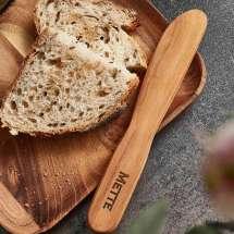 Smørekniv i teak. Dens enkle design, i samspill med treets fine varierte struktur og varme glød, gir hver enkelte smørekniv et enestående, naturlig og rustikt uttrykk.